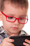 Clever kid is playing with smart cell phone Royalty Free Stock Photos