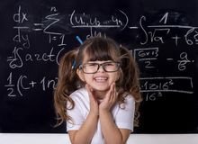 Clever kid in school. Back to school. Smart kid. Studying kid. Pupil with glasses near black blackboard. Studio shoot, Cute kid back to school. Little girl with royalty free stock image