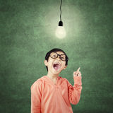 Clever kindergarten student pointing at bright lamp Royalty Free Stock Photo