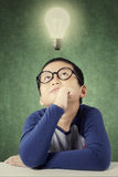 Clever little boy with a bright light bulb Stock Photo
