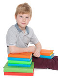 Clever little boy with a pile of books Stock Photos