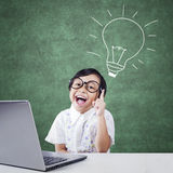 Clever little child with laptop and lamp Royalty Free Stock Image