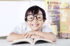 Clever little girl with book smiling at the camera Royalty Free Stock Image