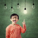 Clever little girl pointing at light bulb Royalty Free Stock Images