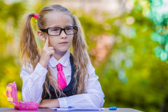 Clever little school girl at desk with notes and Royalty Free Stock Image