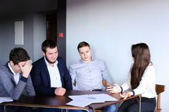 Clever men and young women quarrel and make up tasks for develop. Four company employees guys and girl discuss working moments sitting at table in modern office Stock Photos