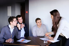 Clever men and young women quarrel and make up tasks for develop. Four company employees guys and girl discuss working moments sitting at table in modern office Stock Image