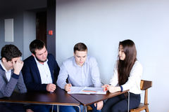 Clever men and young women quarrel and make up tasks for develop. Four company employees guys and girl discuss working moments sitting at table in modern office Stock Photography