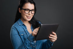 Clever practical woman shopping in the internet. Online activities. Sweet thoughtful attractive lady using her tablet for making purchases while standing on grey royalty free stock photography