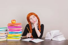 Clever redhead schoolgirl in school uniform consider idea at desk on lesson. Text book on table. Apple lie on book. Back to school royalty free stock images