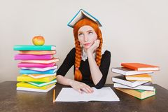 Clever redhead schoolgirl in school uniform think at desk on lesson. Text books on table. Back to school. Notebook on table. Cleve stock photography