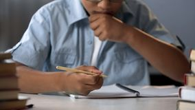 Clever school pupil thinking on solving equation, learning math, knowledge royalty free stock photo