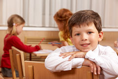 Clever schoolboy. Looking at camera in classroom with his classmates at background stock photos