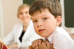 Clever schoolboy. Face of clever schoolboy looking at camera in classroom with his teacher at background Royalty Free Stock Photo