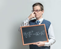 Clever schoolboy in glasses with mathematical equation. The cute smart swagger schoolboy teenager in a glasses shows the black chalkboard with the mathematical stock images