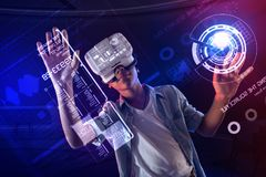 Clever schoolboy touching the screen and using virtual reality glasses. New device. Clever progressive boy smiling and feeling interested while using virtual royalty free stock image