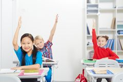 Clever kids. Clever schoolkids raising their hands at lesson to answer question of teacher royalty free stock photos