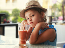 Clever serious kid girl drinking vitamin smoothie juice in stree Stock Photos