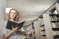 Clever student with open book reading it in college library Royalty Free Stock Photo