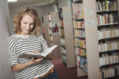 Clever student with open book reading it in college library Stock Photos