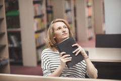 Clever student with open book reading it in college library Stock Image