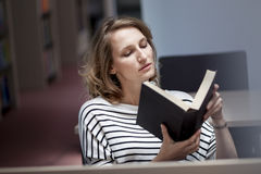 Clever student with open book reading it in college library Royalty Free Stock Images