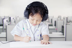 Clever student studying while wearing headphones Royalty Free Stock Image
