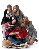Clever students. The clever young people sitting with books on a white background stock image
