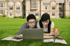 Clever students studying at park. Two clever high school student lying at the school yard while studying together with laptop and books Royalty Free Stock Images