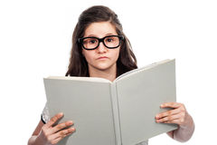 Clever Teenage Girl Reading a Big Book. Brainy clever teenager with big glasses reading a big book on white background Royalty Free Stock Images