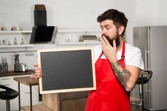 Clever ways to organize kitchen. Cook hold blank chalkboard copy space. Secret tips. Useful information. Man bearded. Hipster red apron stand in kitchen royalty free stock image