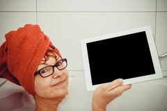 Clever woman in bathtub with tablet computers, space for text Stock Image