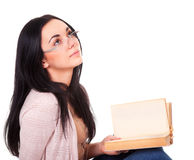 Clever woman with book looks up Stock Photos