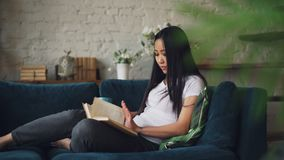 Clever young lady with long dark hair is reading book and holding cup of coffee sitting on couch in living room in. Beautiful flat enjoying solitude and peace stock video footage