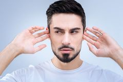 Clever young man rejecting to hear unpleasant unnecessary information Stock Photography