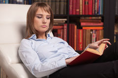 Clever young woman reads book at home. Royalty Free Stock Photography