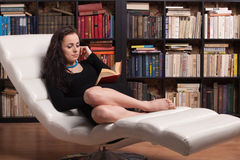Clever young woman reads book at home. Royalty Free Stock Image