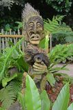 The carved face of a tribal god made from a tropical nut i na Singapore jungle environment. A cleverly carved statue of a tribal god made out of a tree nut in a Royalty Free Stock Image