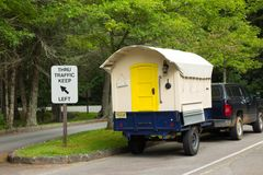 A cute hand-built camper hitched to a car. A cleverly constructed little home on wheels as seen at a campground in the summertime Stock Photos