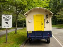 A cute hand-built camper hitched to a car. A cleverly constructed little home on wheels as seen at a campground in the summertime Stock Photo