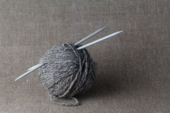 Clew of gray yarn with needle Royalty Free Stock Photos