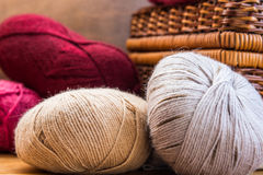 Clews balls of natural red beige grey wool yarn, wicker crafts basket, cozy atmosphere, authentic style. Close up stock images