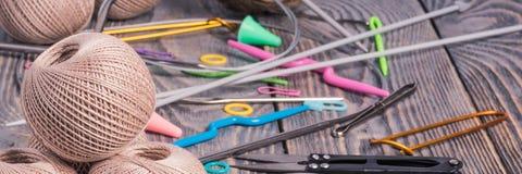 Clews do fio, das agulhas de confec??o de malhas, das tesouras e dos grampos no fundo de madeira fotos de stock
