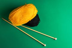 Clews of yellow black fine wool yarn wooden knitting needles on dark green background warm autumn color palette. Crafts hobby. Clothes making fashion concept stock photography