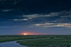 Cley的沼泽地下海作为太阳落山,Cley,北诺福克区,英国- 2012年8月17日 库存图片