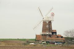 Cley windmill standing beside the marsh. stock image