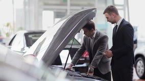 Cliënt die de motor van de auto inspecteren stock footage