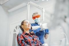 Cliënt die terwijl tandarts in blauwe eenvormige holdingsröntgenstraal glimlachen royalty-vrije stock foto