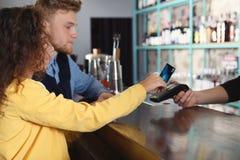 Cliënten die creditcardmachine voor niet-contante betaling met behulp van stock afbeelding
