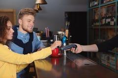 Cliënten die creditcardmachine voor niet-contante betaling met behulp van stock foto's